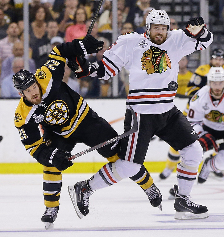 . Boston Bruins defenseman Andrew Ference (21) and Chicago Blackhawks center Patrick Sharp (10) fight for position as the puck passes during the first period in Game 6 of the NHL hockey Stanley Cup Finals Monday, June 24, 2013 in Boston. (AP Photo/Elise Amendola)