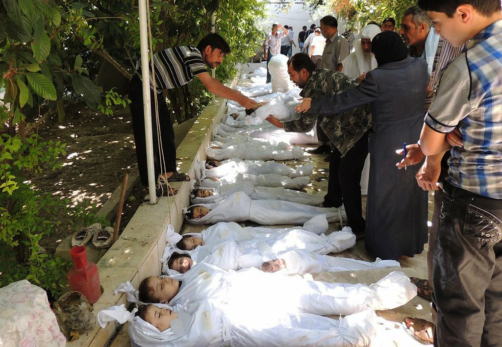 . This citizen journalism image provided by the Local Committee of Arbeen which has been authenticated based on its contents and other AP reporting, shows Syrian citizens trying to identify dead bodies, after an alleged poisonous gas attack fired by regime forces, according to activists in Arbeen town, Damascus, Syria, Wednesday, Aug. 21, 2013. (AP Photo/Local Committee of Arbeen)
