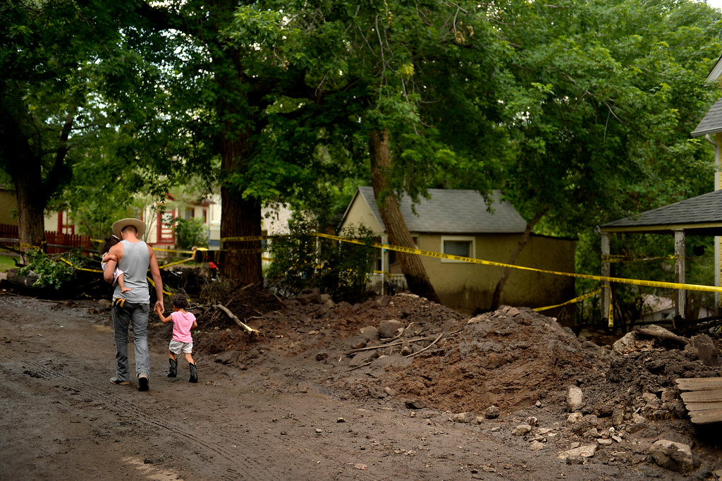 . Manitou Springs, CO. - July 02: Wesley Coplen walks past a wrecked house with a friends children after looking at the damage with her when a flash flood washed through houses, streets and businesses after a downpour over the Waldo Canyon burn scar in El Paso County July 02, 2013 Manitou Springs, Colorado. (Photo By Joe Amon/The Denver Post)