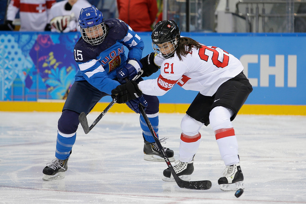 . Minnamari Tuominen of Finland battles Laura Benz of Switzerland for control of the puck during the 2014 Winter Olympics women\'s ice hockey game at Shayba Arena, Wednesday, Feb. 12, 2014, in Sochi, Russia. (AP Photo/Matt Slocum)
