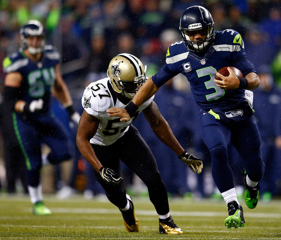 . Quarterback Russell Wilson #3 of the Seattle Seahawks runs with the ball as outside linebacker David Hawthorne #57 of the New Orleans Saints defends during a game at CenturyLink Field on December 2, 2013 in Seattle, Washington.  (Photo by Jonathan Ferrey/Getty Images)