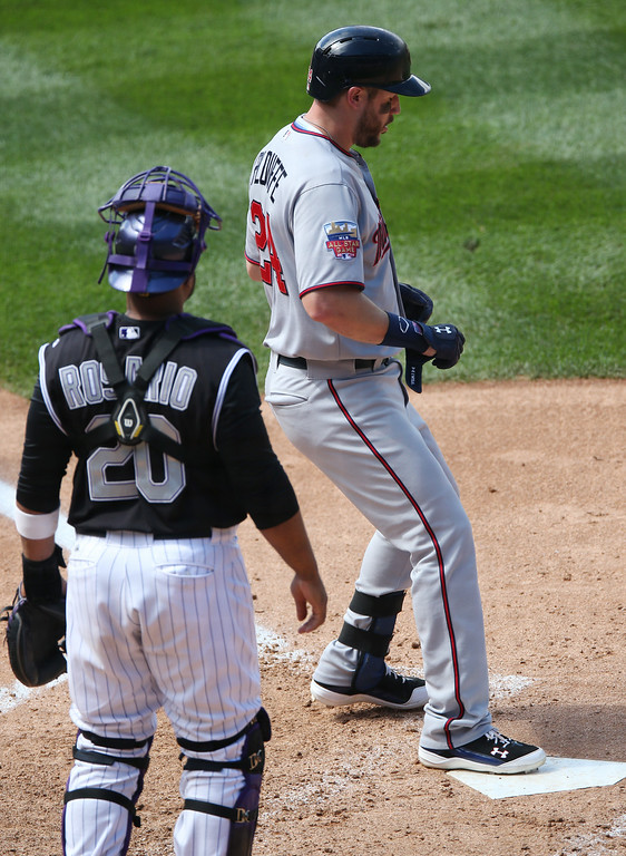 . Minnesota Twins\' Trevor Plouffe, top, touches home plate as Colorado Rockies catcher Wilin Rosario looks on in the fifth inning of an interleague baseball game in Denver on Sunday, July 13, 2014. Plouffe tripled and was waved home on the play because of a throwing error by Rockies second baseman DJ LeMahieu. (AP Photo/David Zalubowski)