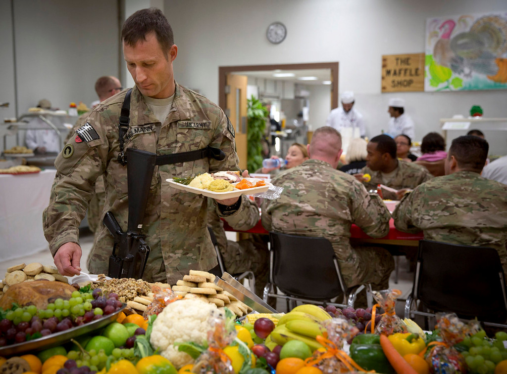 . A U.S. soldier serves himself desert during a Thanksgiving dinner at his base in Kabul, Afghanistan, Thursday, Nov. 28, 2013. It\'s the 12th Thanksgiving in Afghanistan for U.S. troops. (AP Photo/Anja Niedringhaus)