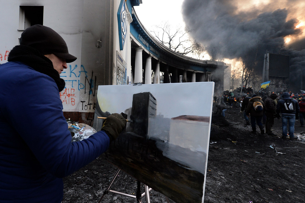 . An anti-government protester paints a scene of fellow protesters clashing with riot police in central Kiev on January 25, 2014.  The anti-government protests in Ukraine on January 25 spread to the north and east of the country as demonstrators sought to seize regional administration offices that have been occupied in over half a dozen regions in the west.     AFP PHOTO / VASILY  MAXIMOV/AFP/Getty Images