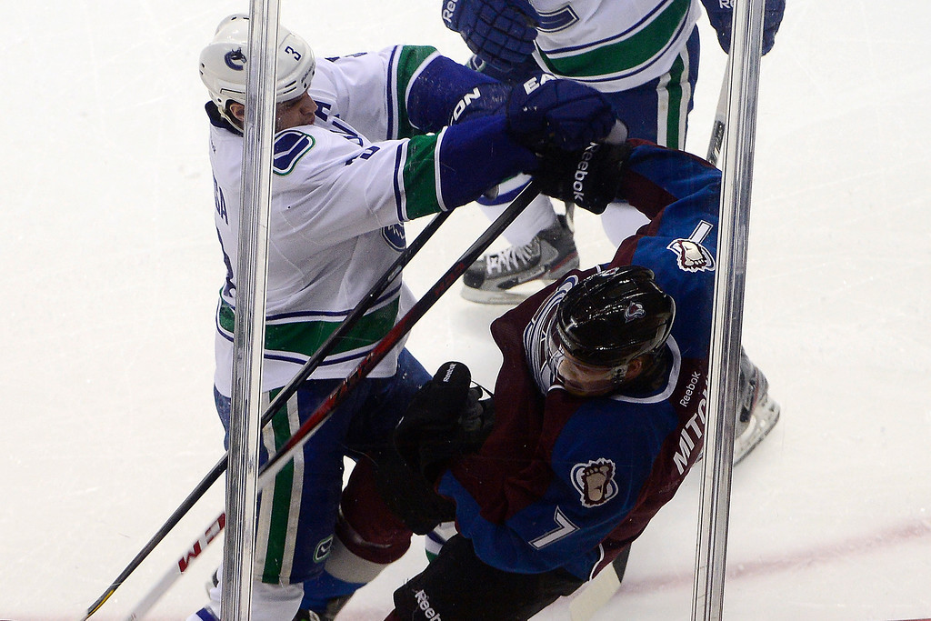 . DENVER, CO - MARCH 24: Kevin Bieksa (3) of the Vancouver Canucks checks John Mitchell (7) of the Colorado Avalanche during the second period of action. Colorado Avalanche versus the Vancouver Canucks at the Pepsi Center. (Photo by AAron Ontiveroz/The Denver Post)