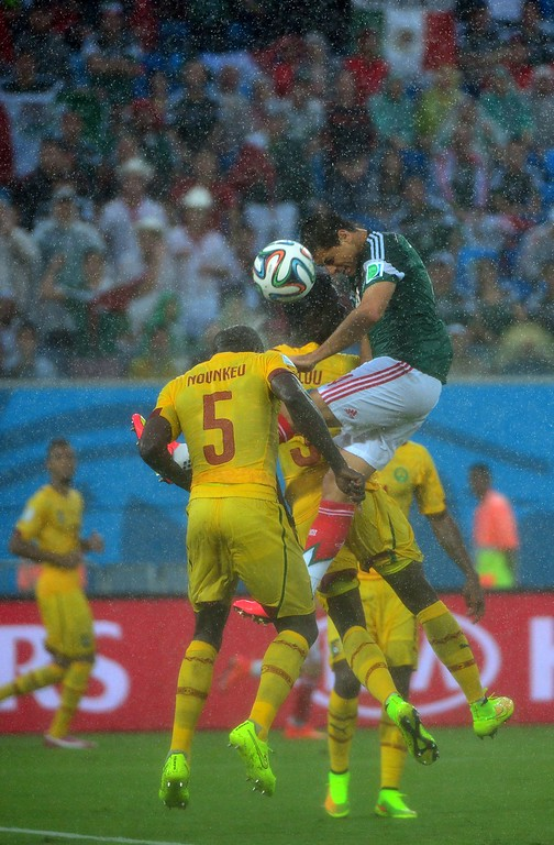 . Mexico\'s forward Javier Hernandez (R) heads the ball with Cameroon\'s defenders Nicolas Nkoulou (back) and Dany Nounkeu (L) during the Group A football match between Mexico and Cameroon at the Dunas Arena in Natal during the 2014 FIFA World Cup on June 13, 2014.   AFP PHOTO / YURI CORTEZ/AFP/Getty Images