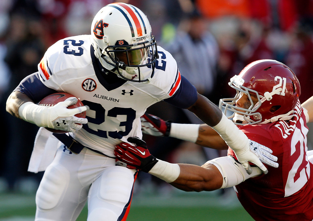 . Auburn running back Onterio McCalebb (23) stiff arms Alabama defender Brent Calloway (21) during a kick return during the first half of their NCAA college football game on Saturday, Nov. 24, 2012, in Tuscaloosa, Ala. (AP Photo/Butch Dill)