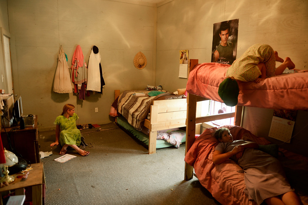 . Sarai Newman, 14, left, and her younger sisters, Shekinah, 6, top, and Selah, 10, take a break during the heat of the day in Trenton, Mo., Tuesday, September 24, 2013. Five sisters share the room, that was added onto the barn, at the families farm. The parents and two other children stay in a temporary mobile home trailer as the family builds a new home. (Photo By RJ Sangosti/The Denver Post)