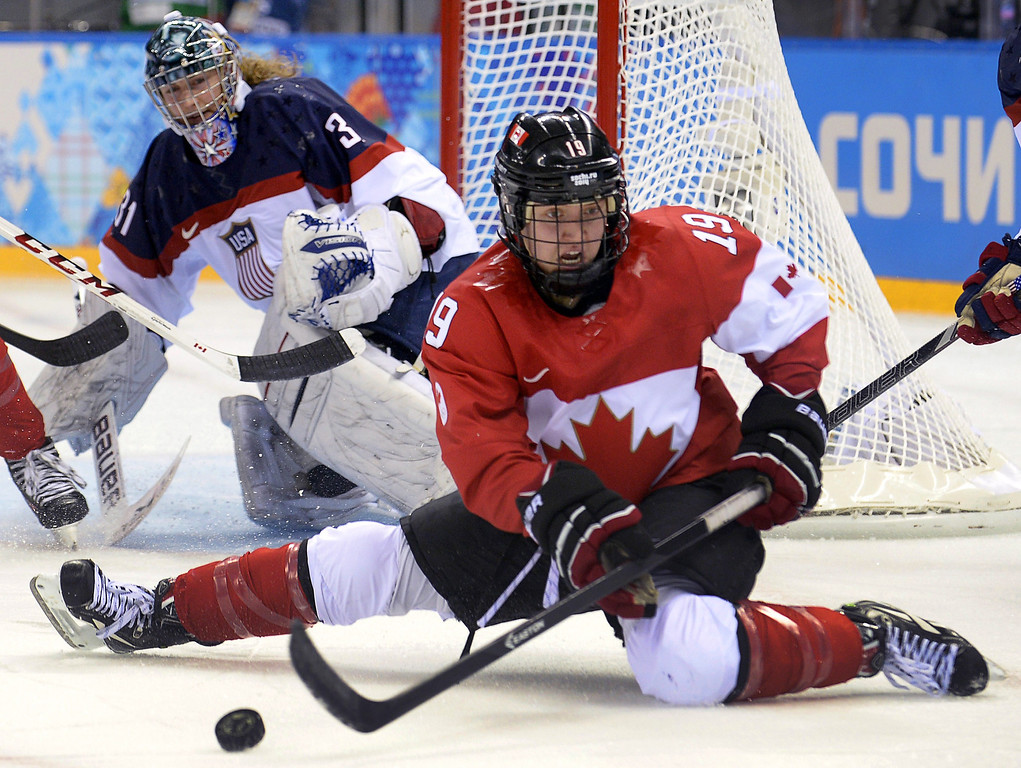. Canada\'s Brianne Jenner (R) vies for the puck with in front of US goalkeeper Jessie Vetter during the Women\'s Ice Hockey Group A match between Canada and USA at the Sochi Winter Olympics on February 12, 2014 at the Shayba Arena. ALEXANDER NEMENOV/AFP/Getty Images