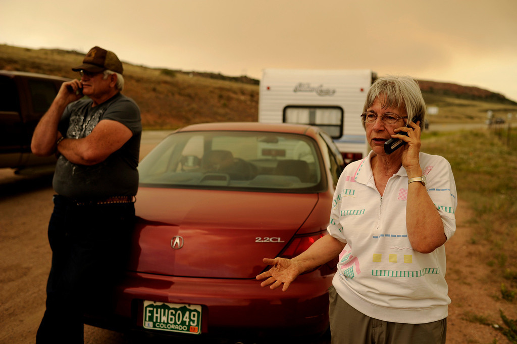 . Evacuees Rodger Zorko, left, and Marlene Smith of Glacier View make phone calls at the corner of HWY 287 and Redfeather Lakes Rd. and checks smoke of High Park Fire in Larimer County, Colo, Friday, June 22. Larimer County forced officials to send out 733 new evacuation notices Friday, as a spot fire north of the blaze raged out of control. Hyoung Chang, The Denver Post