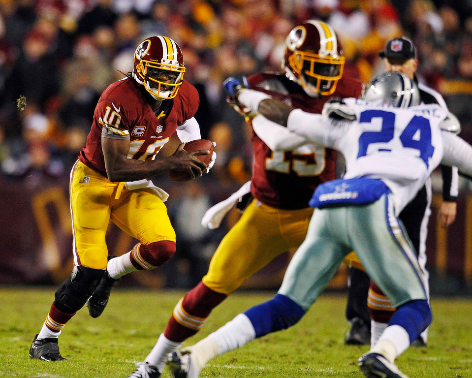 . Washington Redskins quarterback Robert Griffin III (L) runs against the Dallas Cowboys in the first half of their NFL football game in Landover, Maryland December 30, 2012.     REUTERS/Gary Cameron