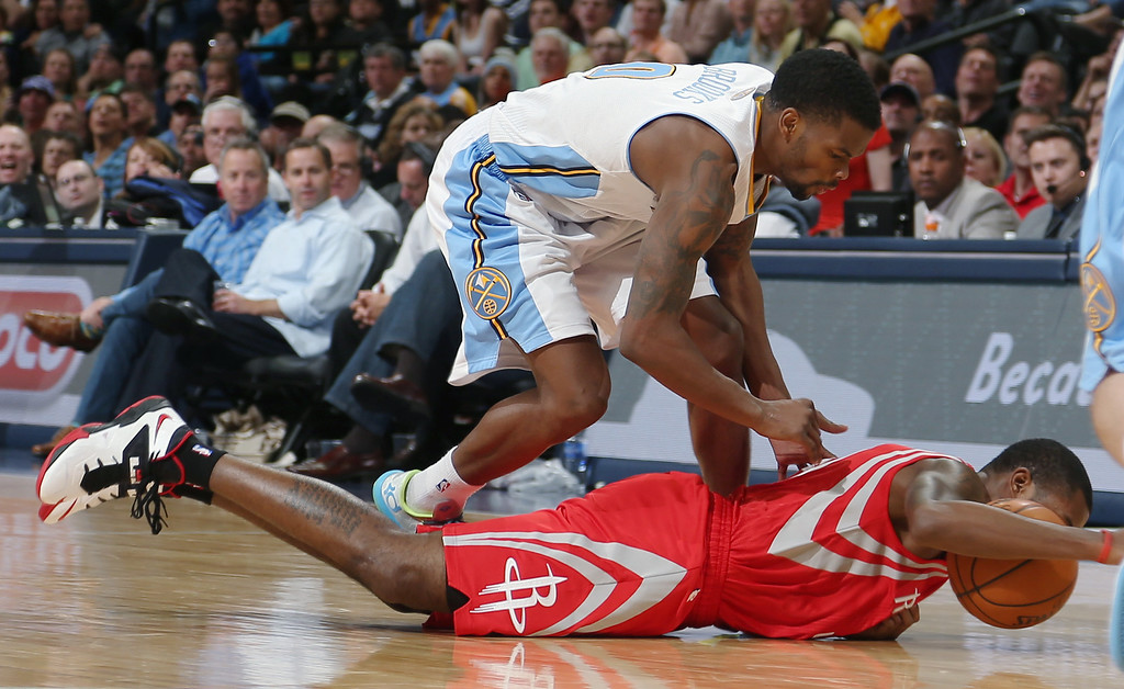 . Houston Rockets guard Troy Daniels, bottom, pulls in a loose ball as Denver Nuggets guard Aaron Brooks covers in the fourth quarter of the Nuggets\' 123-116 victory in an NBA basketball game in Denver on Wednesday, April 9, 2014. (AP Photo/David Zalubowski)