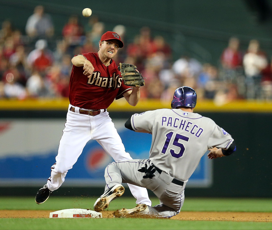 . Infielder Josh Wilson #10 of the Arizona Diamondbacks throws over the sliding Jordan Pacheco #15 of the Colorado Rockies as he attempts to complete an unsuccessful double play during the seventh inning of the MLB game at Chase Field on April 28, 2013 in Phoenix, Arizona.  (Photo by Christian Petersen/Getty Images)