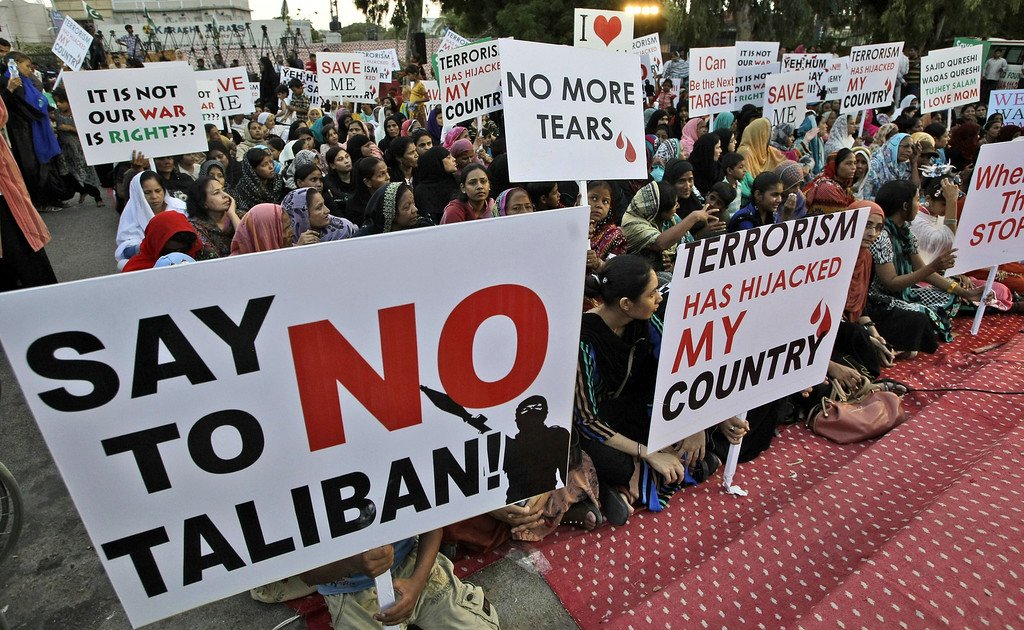 . Pakistani workers of political party Muttahida Qaumi Movement (MQM), hold placards during a protest to condemn the killing of foreign tourists by militants, in Karachi, Pakistan, Sunday, June 23, 2013. Islamic militants wearing police uniforms shot to death many foreign tourists and one Pakistani before dawn as they were visiting one of the world\'s highest mountains in a remote area of northern Pakistan that has been largely peaceful, officials said. (AP Photo/Fareed Khan)