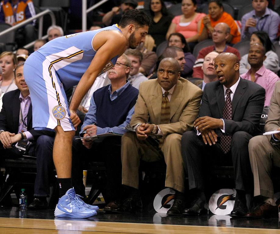 . Denver Nuggets shooting guard Evan Fournier (94) talks to head coach Brian Shaw in the first quarter during an NBA basketball game against the Phoenix Suns , Sunday, Jan. 19, 2014, in Phoenix. (AP Photo/Rick Scuteri)