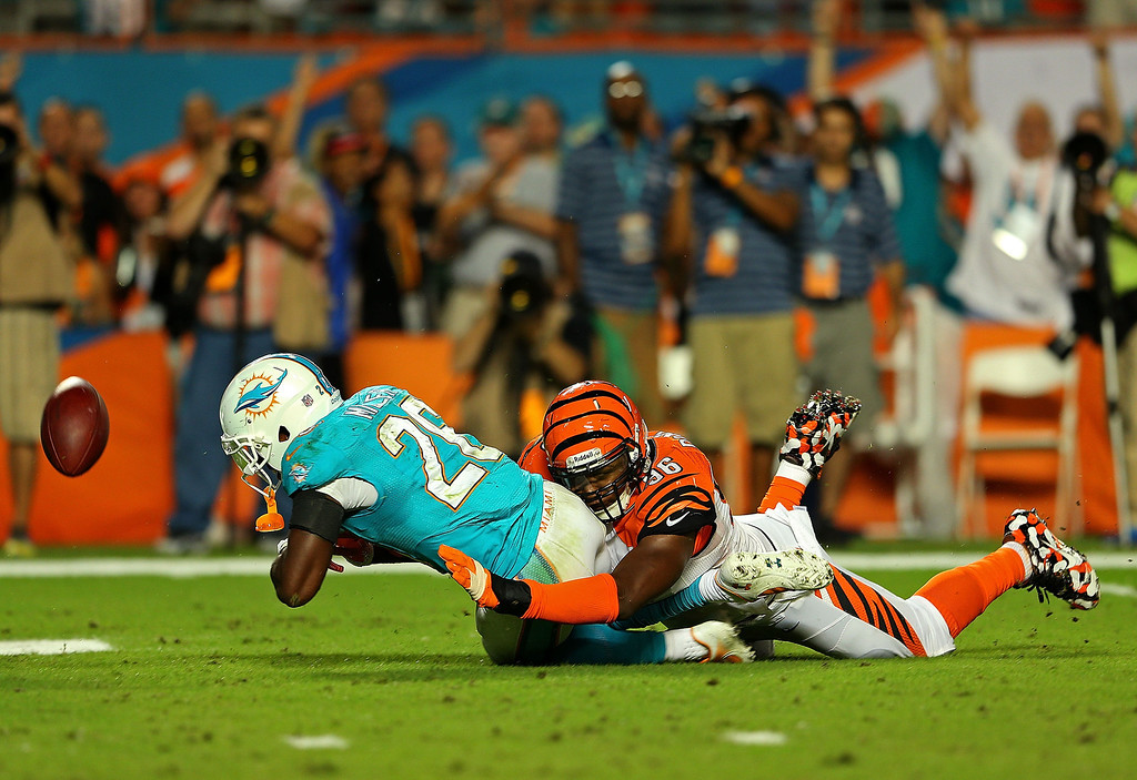 . MIAMI GARDENS, FL - OCTOBER 31: Nolan Carroll #28 of the Miami Dolphins has the ball klnocked out by Trevor Robinson #66 of the Cincinnati Bengals during a game  at Sun Life Stadium on October 31, 2013 in Miami Gardens, Florida.  (Photo by Mike Ehrmann/Getty Images)