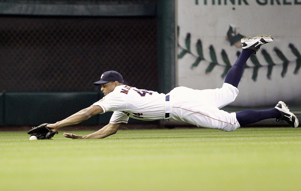 . Justin Maxwell #44 of the Houston Astros makes a diving catch on a line drive by Ian Kinsler #5 of the Texas Rangers in the third inning on Opening Day at Minute Maid Park on March 31, 2013 in Houston, Texas.  (Photo by Bob Levey/Getty Images)