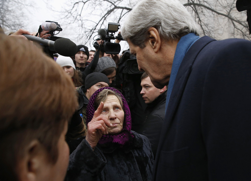 """. U.S. Secretary of State John Kerry clasps hands with an elderly woman who was speaking with him, during his visit to the Shrine of the Fallen in Kiev on March 4, 2014. The Shrine of the Fallen, located on Institutska Street, honors the fallen \""""Heroes\"""" of the \""""Heavenly Sotnya\"""" (Hundred). Over the course of the EuroMaidan protests, almost 100 protesters were killed by police. Most of them died on February 20 killed by sniper or automatic weapons fire on Institutska Street.  US Secretary of State John Kerry arrived in Kiev Tuesday for talks with Ukraine\'s new interim government, amid an escalating crisis in Crimea. His visit came as the United States said it would provide $1 billion to financially-stricken Ukraine as part of an international loan.  With the Black Sea peninsula of Crimea under near complete control by pro-Russian forces, US officials said Moscow could face sanctions within days. AFP PHOTO / POOL - Kevin LAMARQUE/AFP/Getty Images"""