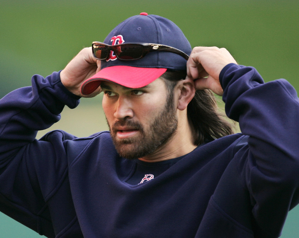 . Boston Red Sox center fielder Johnny Damon adjusts his hat during a workout, in preparation for Game 3 of the World Series, at Busch Stadium in St. Louis, Monday, Oct. 25, 2004. The Red Sox lead the series 2-0. Game 3 will be played Tuesday. (AP Photo/Al Behrman)