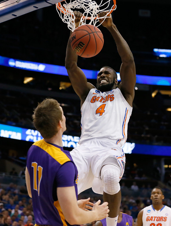 . ORLANDO, FL - MARCH 20:  Patric Young #4 of the Florida Gators dunks over Luke Devlin #11 of the Albany Great Danes in the first half during the second round of the 2014 NCAA Men\'s Basketball Tournament at Amway Center on March 20, 2014 in Orlando, Florida.  (Photo by Kevin C. Cox/Getty Images)