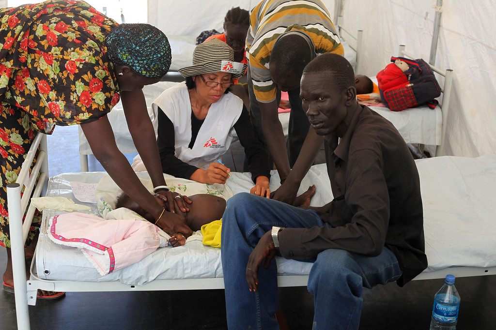 """. This picture released by Medecins Sans Frontieres (MSF, Doctors without Borders) shows MSF nurse Carmelita giving an injection to treat a young patient with malaria in a Juba hospital on December 26, 2013. Two MSF emergency teams comprised of medics, logistics staff and water treatment specialists are running medical activities for people displaced by the recent fighting in Juba, the capital of South Sudan. An estimated 35,000 people fled to two UN compounds and to other gathering points around the city, seeking refuge from the intense fighting that erupted in Juba. After conducting an independent assessment of the needs, two MSF teams are working to address the medical needs of the displaced. \""""A few patients have direct violence wounds, such as gunshots, but the situation has calmed now in Juba and trauma medicine no longer seems to be the main need,\"""" says Forbes Sharp, MSF Emergency Coordinator in Juba. \""""The displaced people do not yet feel safe to return to their homes and they are unwilling to cross town to seek healthcare in regular hospitals and clinics. So we are taking healthcare to them.\""""South Sudan\'s government has agreed to an immediate ceasefire after nearly two weeks of heavy fighting with rebels, East African leaders announced on December 27, 2013. RESTRICTED TO EDITORIAL USE - MANDATORY CREDIT \""""AFP PHOTO / MSF - KIM CLAUSEN\"""" - NO MARKETING NO ADVERTISING CAMPAIGNS - DISTRIBUTED AS A SERVICE TO CLIENTSKim Clausen/AFP/Getty Images"""