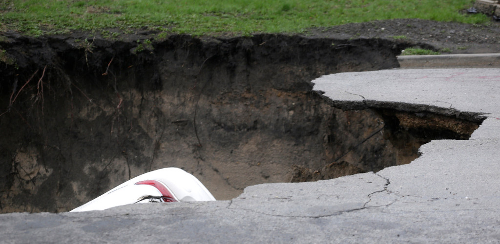 . A section of a car can be seen in a gaping sinkhole that opened up a residential street on Chicago\'s South Side after a cast iron water main dating back to 1915 broke during a massive rain storm Thursday, April 18, 2013, in Chicago. (AP Photo/M. Spencer Green)