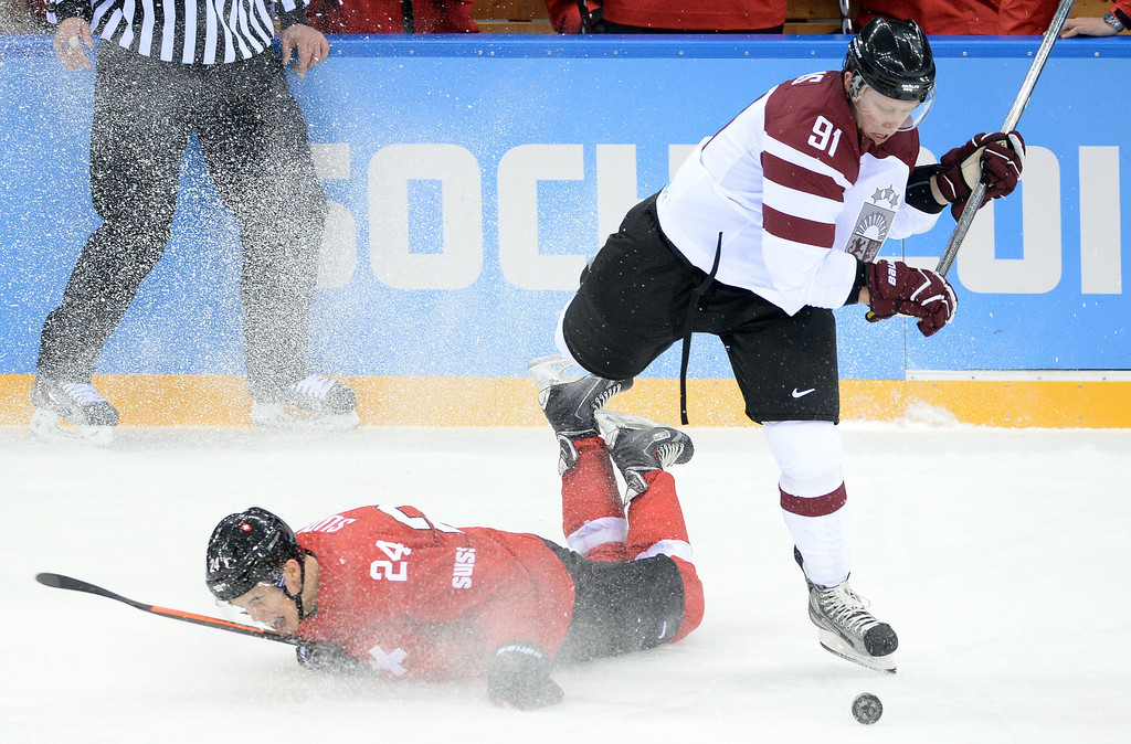 . Latvia\'s Ronalds Kenins (R) vies with Switzerland\'s Reto Suri during the Men\'s Ice Hockey match between Latvia and Switzerland at the Shayba arena during the Sochi Winter Olympics on February 12, 2014. ANDREJ ISAKOVIC/AFP/Getty Images