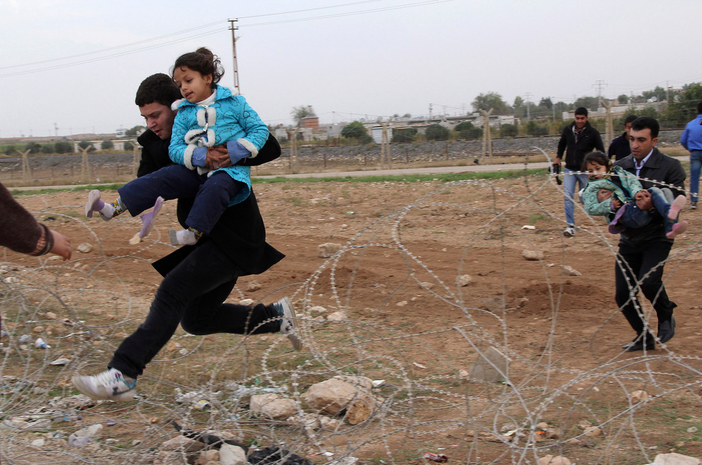 . Syrians jump over barbed wire as they flee from the Syrian town of Ras al-Ain to the Turkish border town of Ceylanpinar, Sanliurfa province, November 9, 2012. REUTERS/Stringer