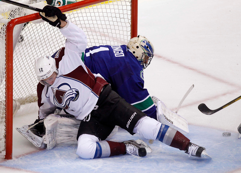 . Colorado Avalanche\'s Chuck Kobasew crashes into Vancouver Canucks goaltender Roberto Luongo during the second period of their NHL hockey game in Vancouver, British Columbia January 30, 2013.   REUTERS/Ben Nelms