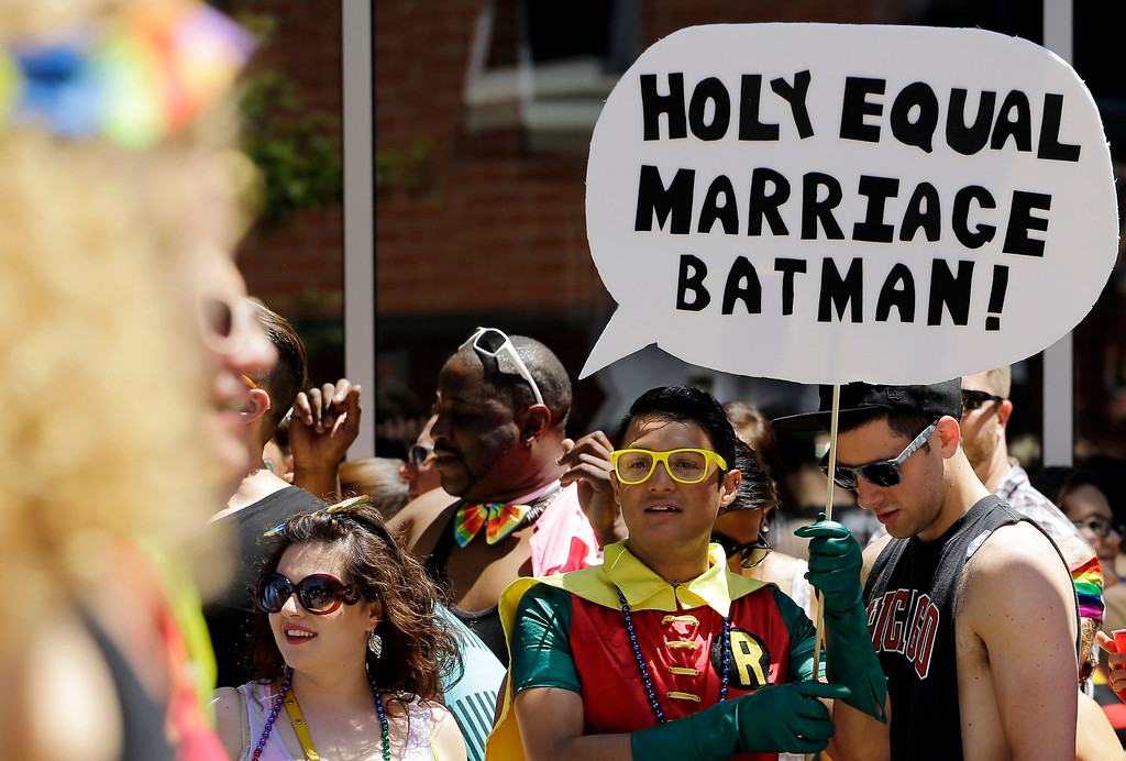 . Max Demian holds a sign as he watches the 45th Annual Chicago Pride Parade in Chicago, Sunday, June 29, 2014. The event, the first since Illinois\' law allowing same-sex marriage went into effect, has 200 registered entrants, with about 1 million expected to participate. (AP Photo/Nam Y. Huh)
