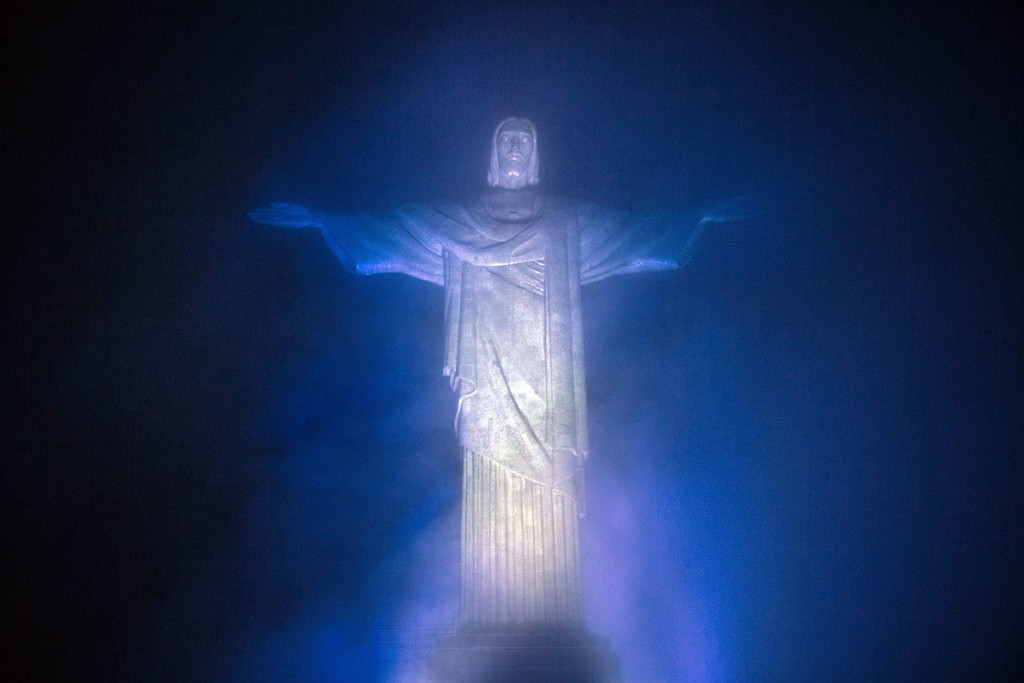 """. View of the statue of Christ the Redeemer illuminated in the colors of the Argentinian national flag in Rio de Janeiro, Brazil, on June 10, 2014, as part of an initiative of tourism organisms of both countries called \""""Fair Play Day\"""". The initiative also consists of illuminating simultaneously the Obelisk in Buenos Aires in the colors of the Brazilian national flag to show the world that both countries, traditional football rivals, are united.  AFP PHOTO / YASUYOSHI CHIBA/AFP/Getty Images"""
