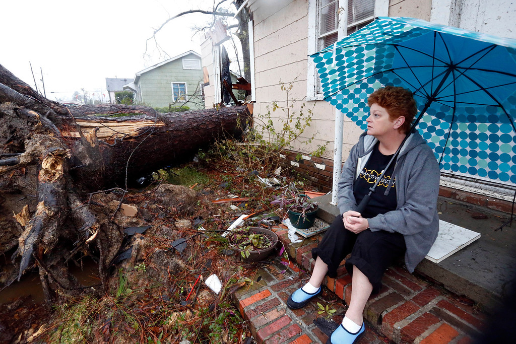 . Hellen Chmiel, 57, sits in front of the remains of her home in Hattiesburg, Miss., Monday, Feb. 11, 2013, following a Sunday afternoon tornado that caused much damage throughout the South Mississippi college town. Chmiel, who was out of her house when the tornado struck, said the large pine tree in the front yard completely destroyed her bedroom. (AP Photo/Rogelio V. Solis)