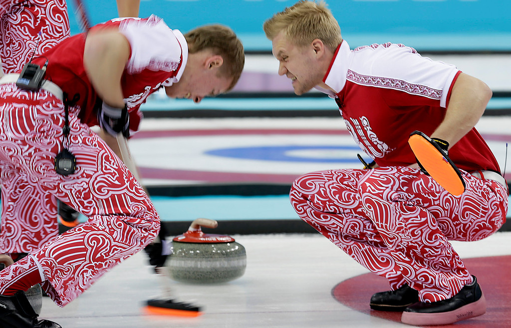 . Russia\'s skip Alexei Stukalskiy, right, shouts to sweeper Evgeny Arkhipov, left, during the men\'s curling competition against the United States at the 2014 Winter Olympics, Friday, Feb. 14, 2014, in Sochi, Russia. (AP Photo/Wong Maye-E)