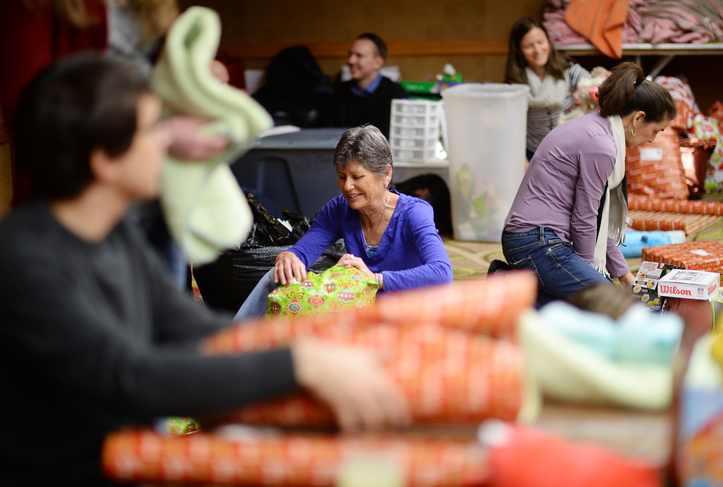 """. DENVER, CO. DECEMBER 21: Chris Lawson of Denver, front center, is wrapping Christmas gift during the annual Father Woody Christmas Party in Denver, Colorado December 21, 2013. In advance of handing out 5,000 gifts, volunteers are doing a \""""wrapping party\"""" at the Sheraton Denver Downtown Hotel. (Photo by Hyoung Chang/The Denver Post)"""