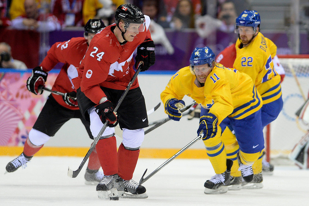 . Corey Perry (24) of Canada controls the puck as Daniel Alfredsson (11) of Sweden reaches for it during the first period of the men\'s ice hockey gold medal game. Sochi 2014 Winter Olympics on Sunday, February 23, 2014 at Bolshoy Ice Arena. (Photo by AAron Ontiveroz/ The Denver Post)