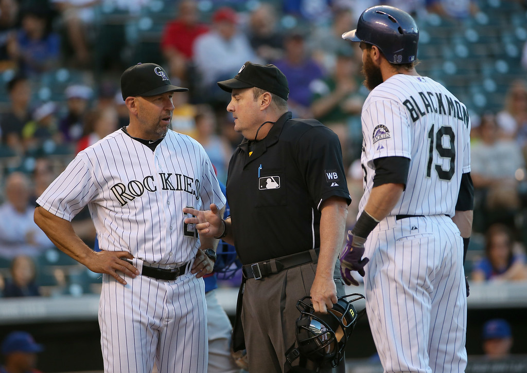 . DENVER, CO - AUGUST 05:  Manager Walt Weiss #22 of the Colorado Rockies questions the call with homeplate umpire Marty Foster after Charlie Blackmon #19 of the Colorado Rockies grounded out bunting against the Chicago Cubs in the first inning at Coors Field on August 5, 2014 in Denver, Colorado.  (Photo by Doug Pensinger/Getty Images)