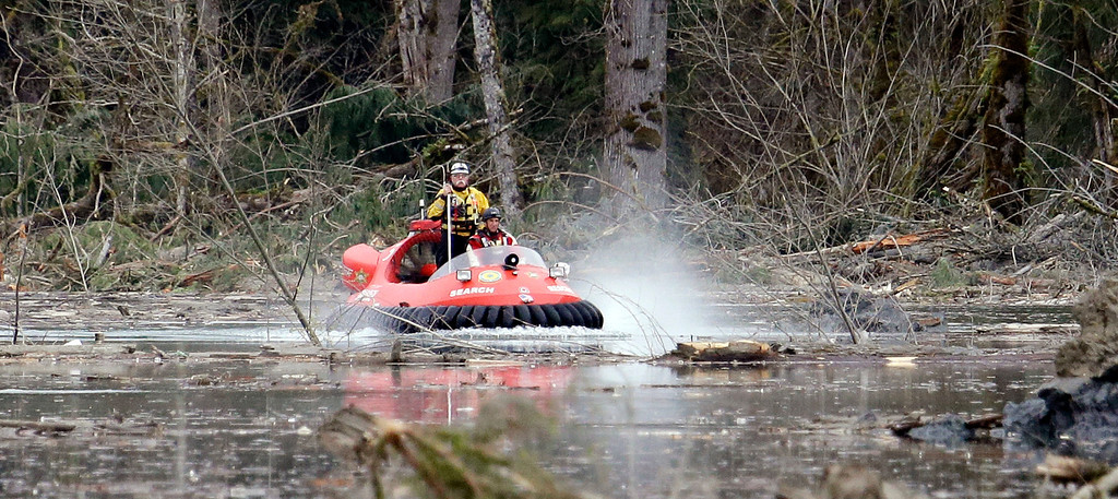 . Searchers work from aboard a hovercraft while looking through debris from a mudslide, Tuesday, March 25, 2014, in Oso, Wash. (AP Photo/Elaine Thompson)