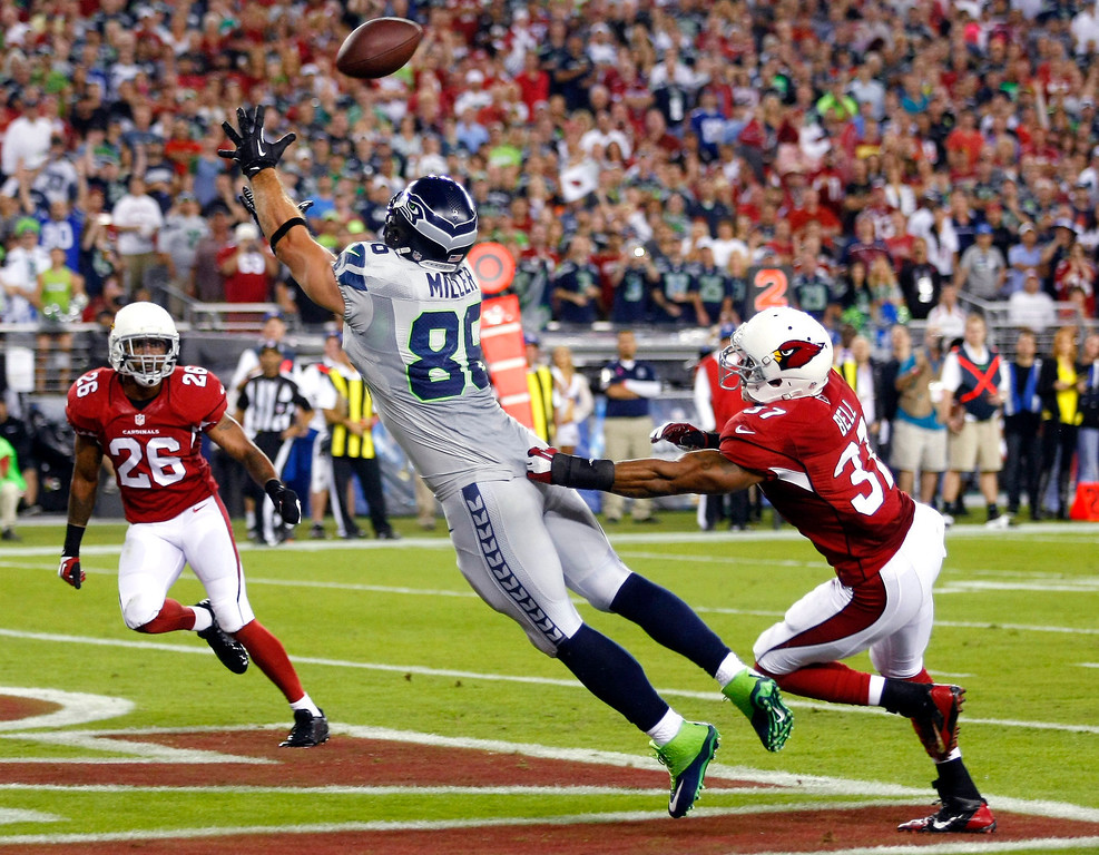. Seattle Seahawks tight end Zach Miller (86) pulls in a touchdown pass as Arizona Cardinals strong safety Yeremiah Bell (37) and Rashad Johnson (26) defend during the first half of an NFL football game, Thursday, Oct. 17, 2013, in Glendale, Ariz. (AP Photo/Rick Scuteri)