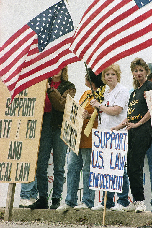 . Demonstrators in favor of the Department of Alcohol, Tobacco and Firearms stand with signs and flags on a roadway that leads to the Branch Davidian compound near Waco, Texas on Sunday, March 29, 1993. (AP Photo/George Widman)