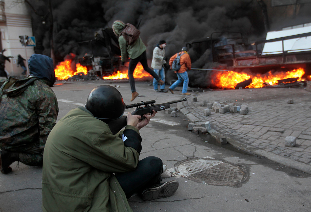 . An anti-government protester shoots during clashes with riot police outside Ukraine\'s parliament in Kiev, Ukraine, Tuesday, Feb. 18, 2014. Thousands of angry anti-government protesters clashed with police in a new eruption of violence following new maneuvering by Russia and the European Union to gain influence over this former Soviet republic.(AP Photo/Sergei Chuzavkov)