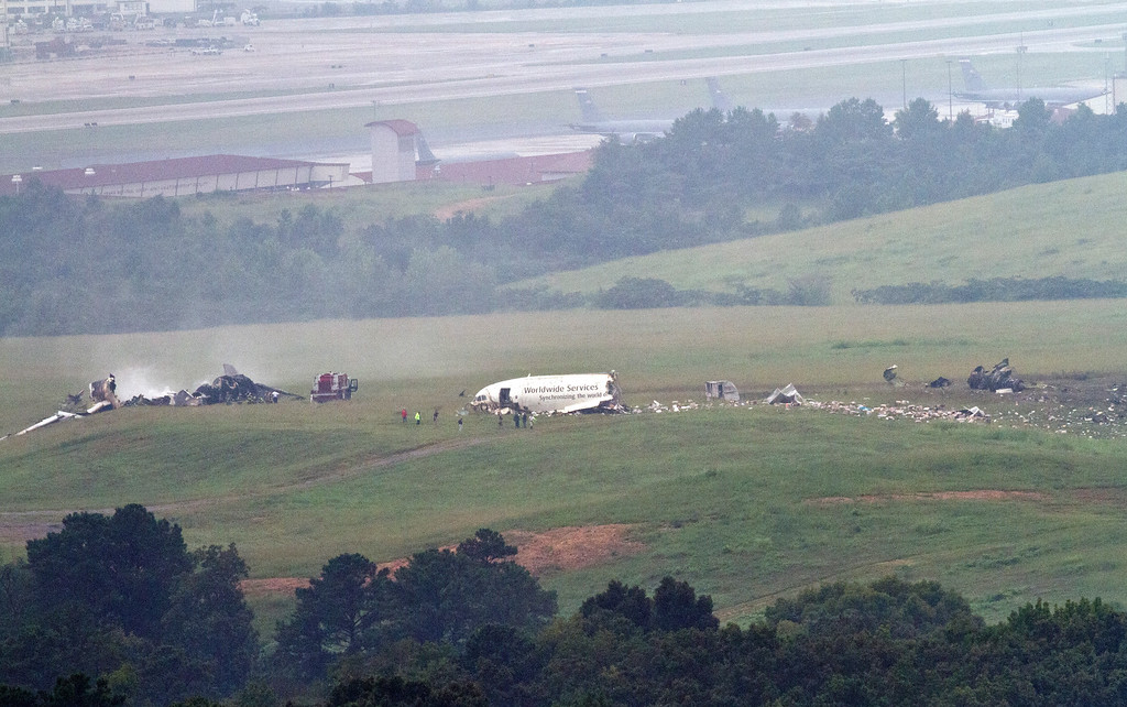 . Investigators search through the debris at the scene of a UPS cargo plane crash at the Birmingham International airport in Birmingham, Ala. on Wednesday, Aug. 14, 2013. (AP Photo/Butch Dill)