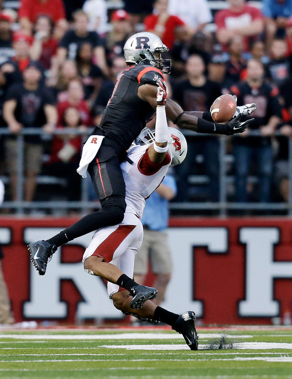 . Rutgers wide receiver Brandon Coleman, left, catches a pass late in the fourth quarter over Arkansas corner back Tevin Mitchel during an NCAA college football game in Piscataway, N.J., Saturday, Sept. 21, 2013. Rutgers won 28-24. (AP Photo/Mel Evans)
