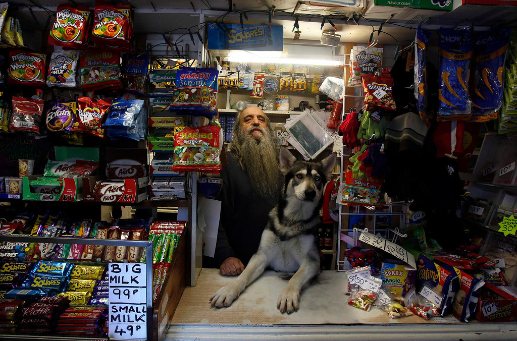 . William Mulhall poses for a photograph in his old curiosity shop in the small seaside village of Ardglass in Co.Down January 15, 2012. Despite the tiny population the shop stays open 24 hours a day, 365 days of the year, to cater for the fishermen who work round the clock. Mulhall, who is an acclaimed local artist, paints in his shop which doubles as his studio.   REUTERS/Cathal McNaughton
