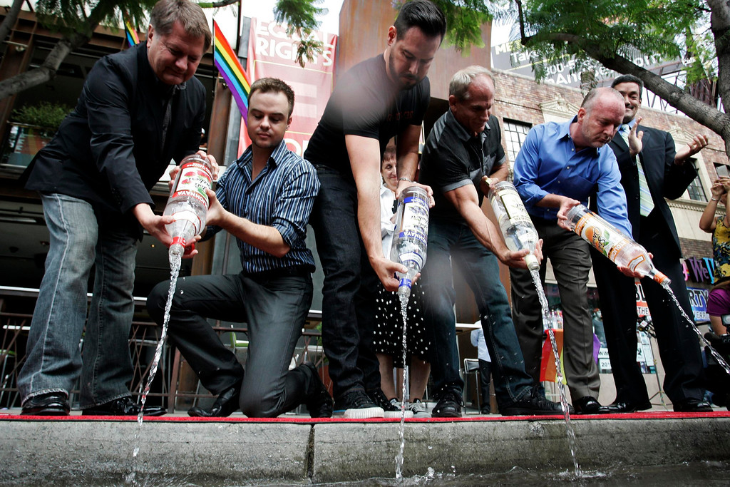 . Michael Niemeyer (L-R), Matthew Ervin, Alfredo Diaz, Richard Grossi, Rodney Scott, and John Duran empty Russian vodka bottles filled with water, into the gutter during a news conference at Micky\'s nightclub in West Hollywood, California August 1, 2013. Bar owners, city officials and members of lesbian, gay, bisexual, and transgender (LGBT) organizations participated in the event to announce a boycott of Russian vodkas to protest new laws in Russia targeting homosexuals, according to a news release by the organizers. REUTERS/Jonathan Alcorn