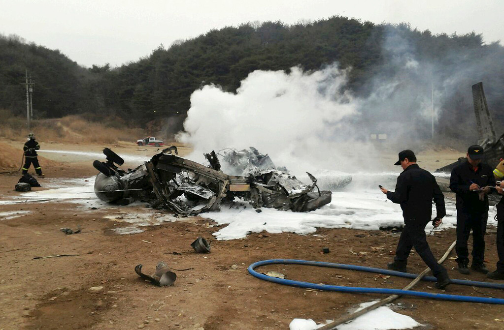 """. A firefighter tries to extinguish a U.S. Marine helicopter CH-53E Super Stallion helicopter after it made a \""""hard landing\"""" during an exercise called SsangYong, a Korean Marine Exchange Program and part of the Foal Eagle exercise in Chulwon, north of Seoul, South Korea, Tuesday, April 16, 2013. Twenty-one personnel were on board the helicopter, including five crew members, according to a statement from United States Forces Korea. All were taken to the hospital, but 15 were quickly released. The remaining six were in stable condition. (AP Photo/Yonhap) KOREA OUT"""