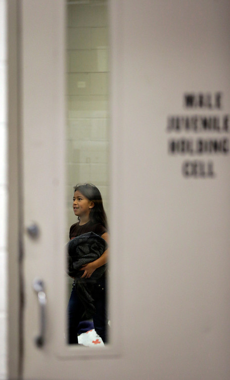 . A detainee is seen through the door of a holding cell at a U.S. Customs and Border Protection processing facility, Wednesday, June 18, 2014, in Brownsville,Texas. (AP Photo/Eric Gay, Pool)