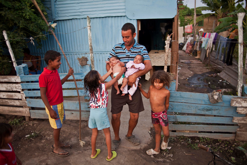 """. In this April 8, 2013 photo, Eduardo Gonzalez, 30, holds his babies outside his aluminum shack in a squatter\'s settlement near Tacarigua, Venezuela. Outside Venezuela\'s capital, power outages, food shortages and unfinished projects abound; important factors heading into Sunday\'s election to replace Venezuela\'s late President Hugo Chavez, who died last month after a long battle with cancer. An estimated 2 million of Venezuela\'s country\'s nearly 30 million people lack permanent homes, and one of Chavez\'s anti-poverty \""""missions\"""" builds them. But it\'s been slow going. The government says it has built 370,500 homes and apartments over the past two years, and more than 3 million people applied for them. (AP Photo/Ramon Espinosa)"""