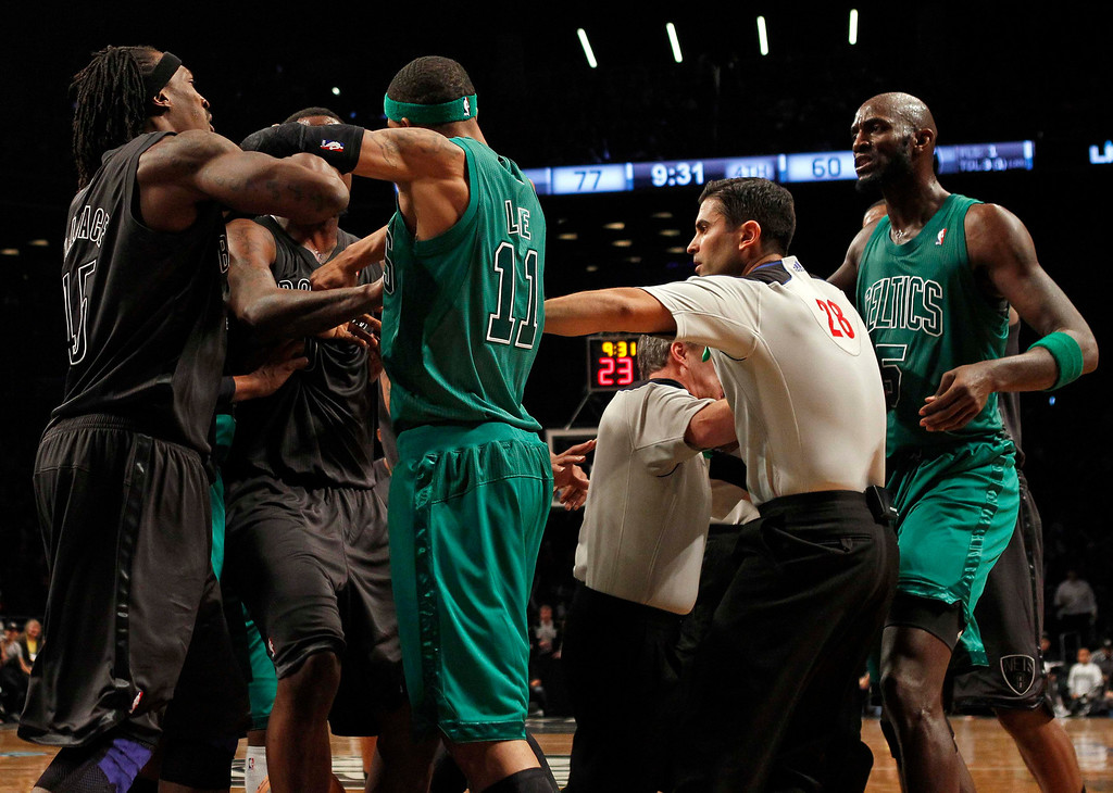 . Boston Celtics forward Kevin Garnett (R) is separated by teammates and officials from Brooklyn Nets forward Gerald Wallace (L) in the fourth quarter of their NBA basketball game in New York, December 25, 2012.    REUTERS/Adam Hunger