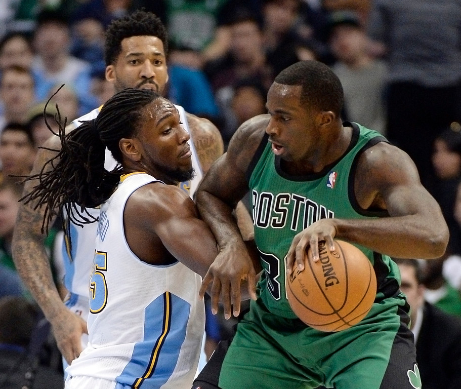 . Boston Celtics power forward Brandon Bass (30) gets guarded closely  by Denver Nuggets power forward Kenneth Faried (35) during the first quarter January 7, 2014 at Pepsi Center. (Photo by John Leyba/The Denver Post)
