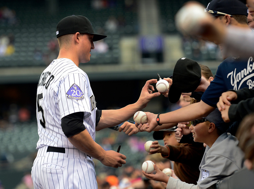 . Jordan Pacheco (15) of the Colorado Rockies signs autographs for fans prior to their game against the New York Yankees May 9, 2013 at Coors Field. (Photo By John Leyba/The Denver Post)